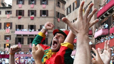 """Jockey of the contrada """"Drago"""" Andrea Mari celebrates after winning the historical Italian horse race Palio di Siena on July 2, 2018, in Siena. (Photo by Vincenzo PINTO / AFP)        (Photo credit should read VINCENZO PINTO/AFP/Getty Images)"""