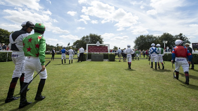 Heading out: jockeys make their way to the paddock to meet connections before the opener