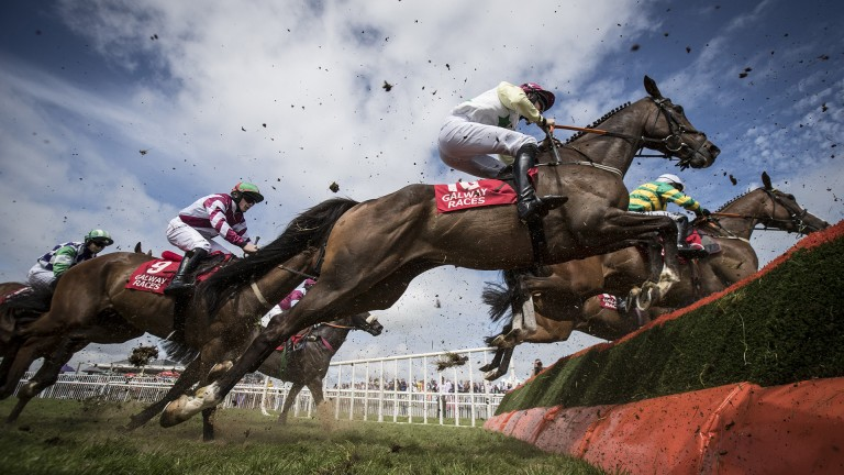 Lovely day for jumping: the 20 runners take a flight of hurdles in the opening 2m½f handicap