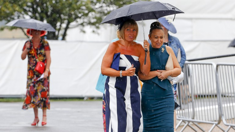Umbrellas up: racegoers take cover from the rain as they arrive for ladies' day