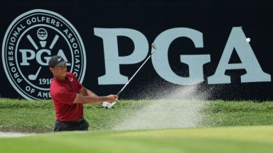 Tiger Woods plays a shot from a greenside bunker at the 2018 US PGA Championship