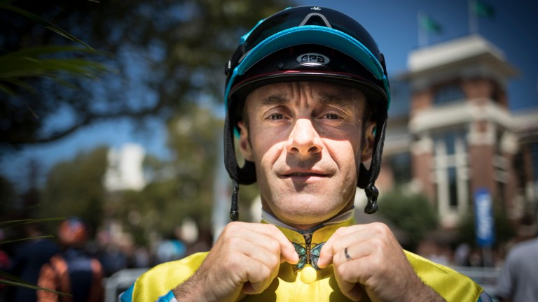 Butterfly boy: French jockey Olivier Peslier shows off his antique butterfly pin before racing on a beautiful afternoon in Normandy