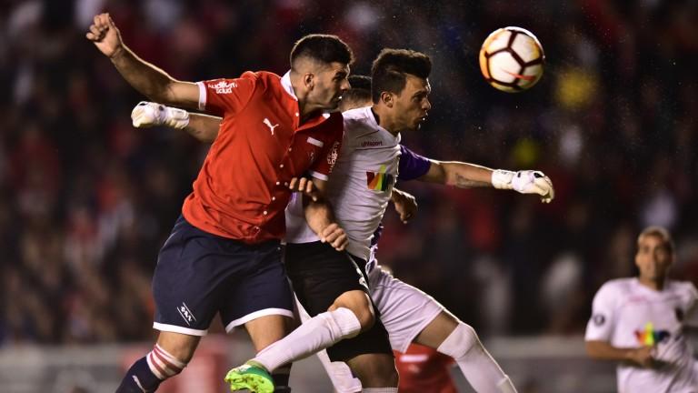 Independiente forward Emmanuel Gigliotti (left) wins a header against Deportivo Lara