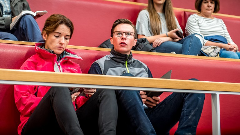 Katie Walsh and Joseph O'Brien split their attention between their phones and the sales ring action