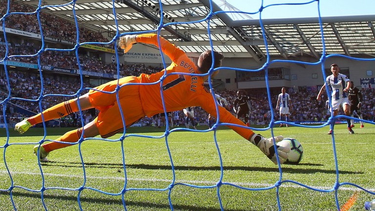 Marcus Bettinelli of Fulham saves a penalty from Pascal Gross of Brighton