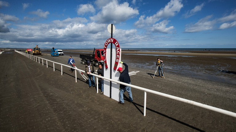 Finishing touches: the winning post is manoeuvred into position for the annual racing fixture on the beach