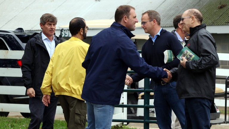 Sheikh Mohammed (yellow) and the Godolphin team exchange handshakes with Coolmore's MV Magnier and Michael Tabor
