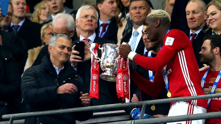 Paul Pogba passes the 2017 EFL Cup trophy to Jose Mourinho