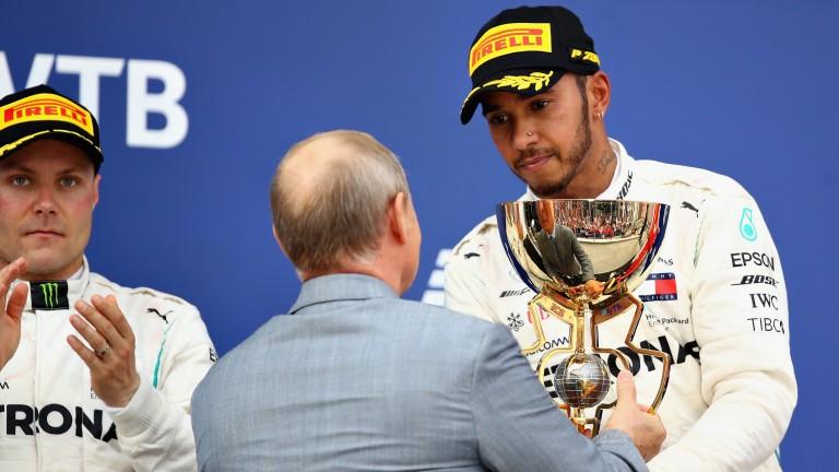 Lewis Hamilton receives the winner's trophy from Vladimir Putin as Valtteri Bottas looks on