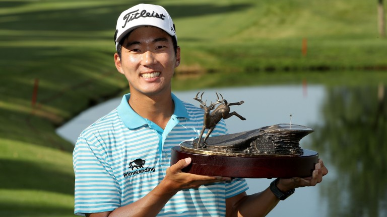 Michael Kim celebrates with the John Deere Classic trophy