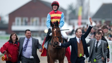 The smile says it all... Nick Scholfield and Hunt Ball are escorted back to the Cheltenham winners' enclosure by owner Anthony Knott (waving) and trainer Kieran Burke (right of picture)