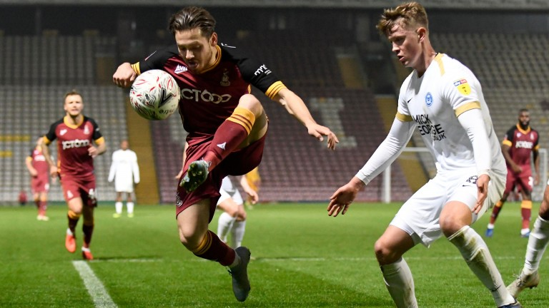 Jack Payne of Bradford jumps to control the ball against Peterborough