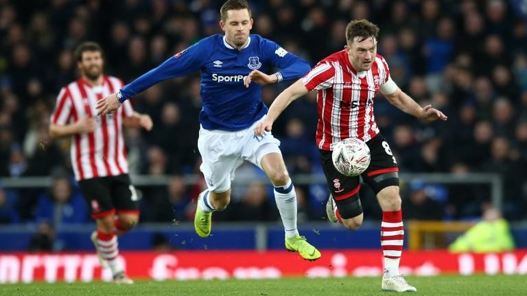 Lincoln's Lee Frecklington battles for possession with Gylfi Sigurdsson of Everton