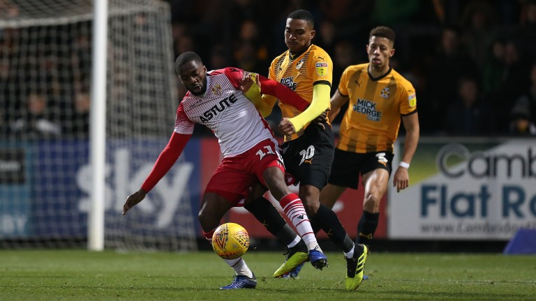 Emmanuel Sonupe of Stevenage attempts to control the ball under pressure from Jevani Brown of Cambridge United