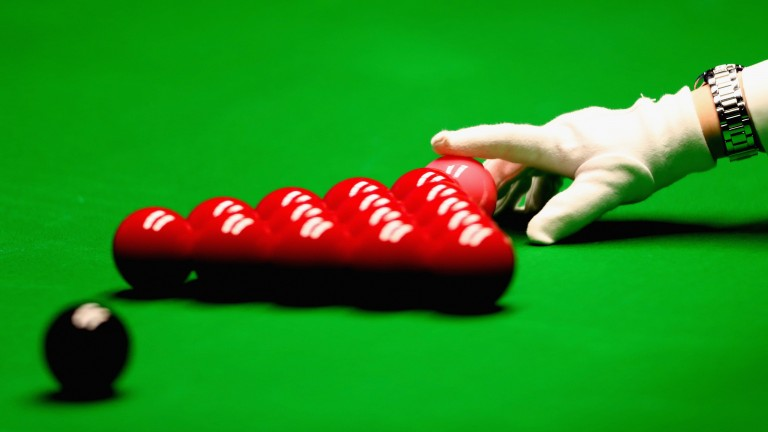The snooker referee places the pink