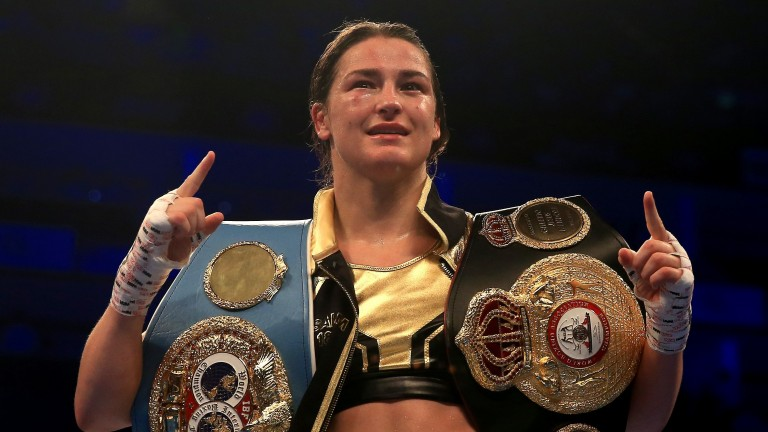 Boxer Katie Taylor celebrates with her world title belts