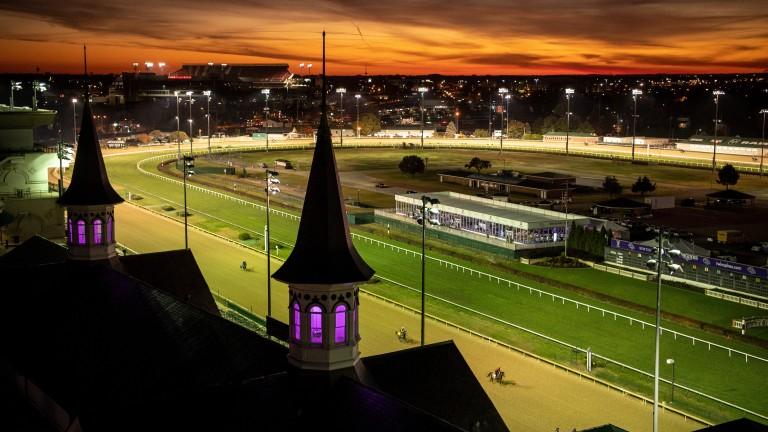 Horses work on the Churchill Downs dirt track at sunrise