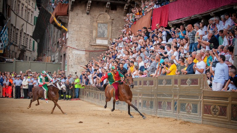 Medieval memories: colourful riders in front of a frantic 'Il Palio' crowd in Siena's Piazza del Campo