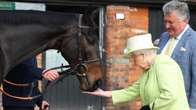 The Queen feeds carrots to Frodon as Paul Nicholls looks on