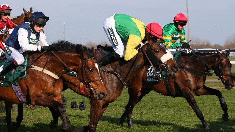 Clinging on: Paddy Kennedy does well to maintain the partnership with eventual runner-up Magic Of Light at Aintree