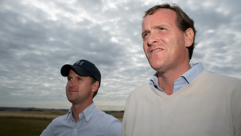 Richard Hannon and assistant Tom Ward (cap) watch work on the gallops at Herridge