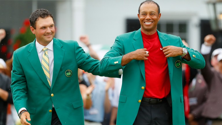 Tiger Woods gets a pat from 2018 champion Patrick Reed as he puts on his fifth Green Jacket