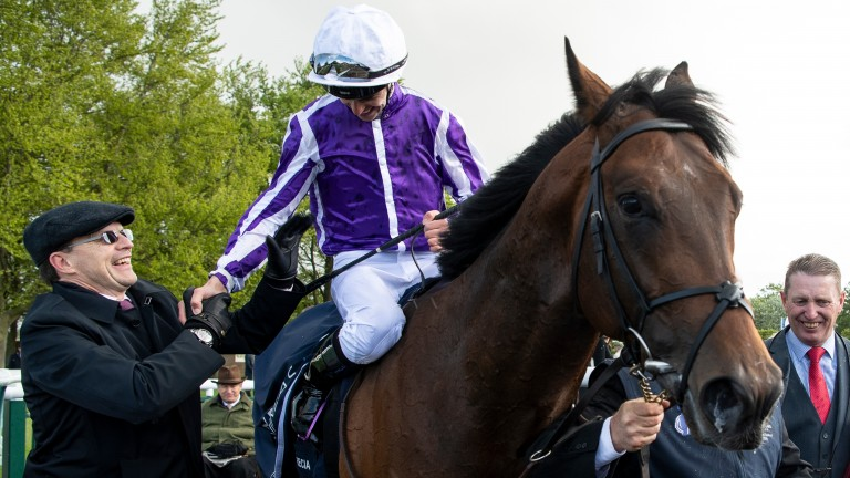 Aidan O'Brien (left) greets son Donnacha after he rode Magna Grecia to Classic victory
