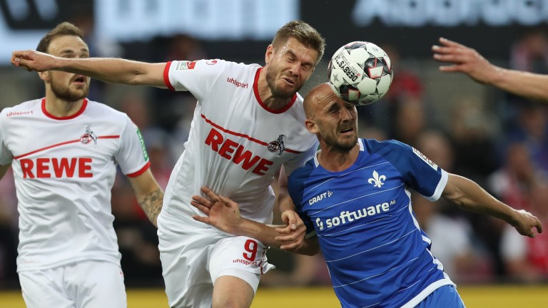 Cologne's Simon Terodde (centre) competes for the ball with Patrick Herrmann of Darmstadt