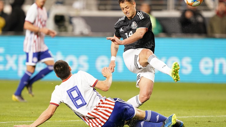 Rodrigo Rojas tackles Javier Hernandez in Paraguay's March match with Mexico