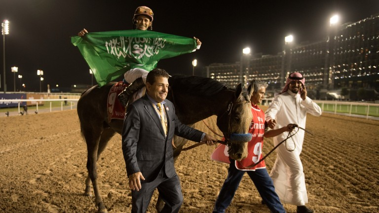 The Saudi Arabian flag is waved by Mike Smith after his win in the 2017 Dubai World Cup aboard Arrogate