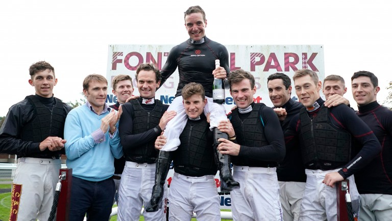 Andrew Tinkler (centre on the shoulders on Jamie Moore) is congratulated by his fellow jockeys after riding his last race at Fontwell