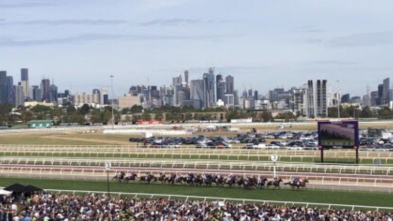 The runners file past the packed stands with the Melbourne skyline in the background
