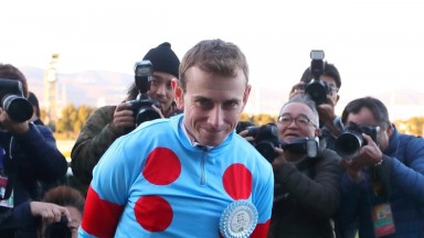 Ryan Moore is surrounded by photographers at Hanshin after winning the Grade 1 Asahi Hai Futurity aboard Salios