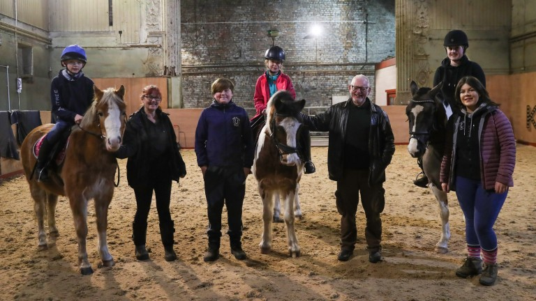 Staff and pupils are all smiles in the riding arena