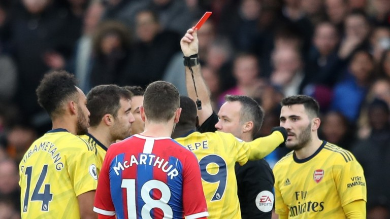 Referee Paul Tierney shows a red card to Pierre-Emerick Aubameyang of Arsenal