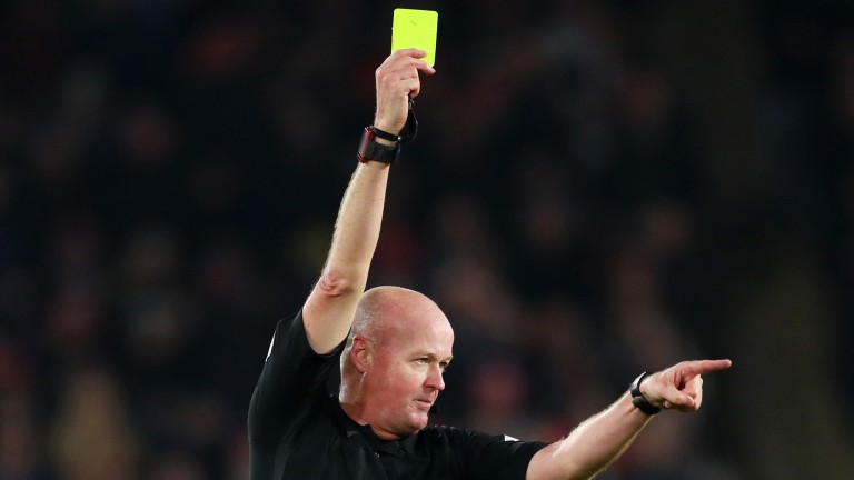 Referee Lee Mason awards a yellow card during the Premier League match between Sheffield United and Manchester City at Bramall Lane