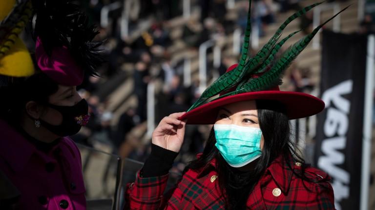 A racegoer dons a face mask at Cheltenham four weeks ago