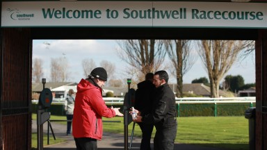 A racegoer sanitises their hands as they arrive at Southwell on Monday