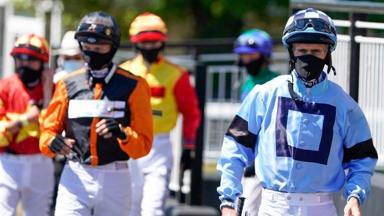 Paul Mulrennan (right) leads the face-masked jockeys out at Newcastle