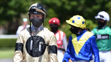 Jockey Charles Bishop leads the jockeys out to the parade ring prior to the opening race at Kempton on Tuesday