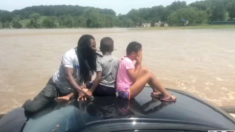 The father moved the children to the roof of the car as the water went over the doors
