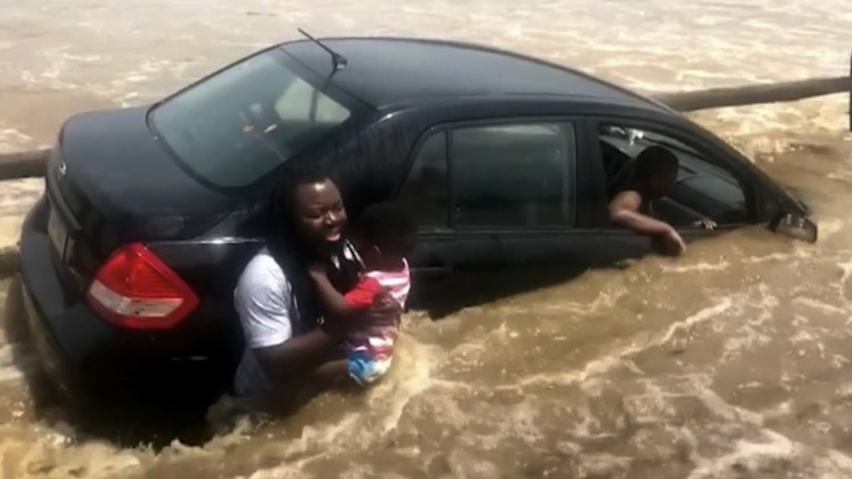 The father holds one of his four children as his car is caught in the rising floodwater in Pennsylvania