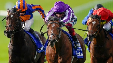NEWMARKET, ENGLAND - OCTOBER 10: Frankie Dettori riding St Mark's Basillica (purple) win The Darley Dewhurst Stakes from Ryan Moore and Wembley (L, orange/blue) at Newmarket Racecourse on October 10, 2020 in Newmarket, England. Owners are allowed to atten
