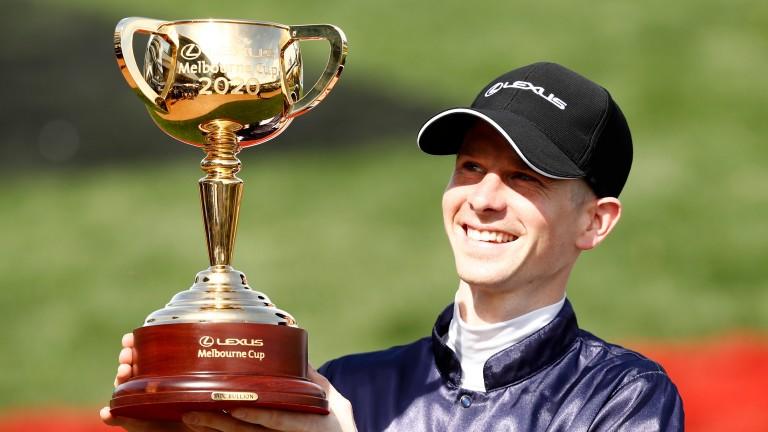 Jye McNeil holds the Melbourne Cup trophy aloft
