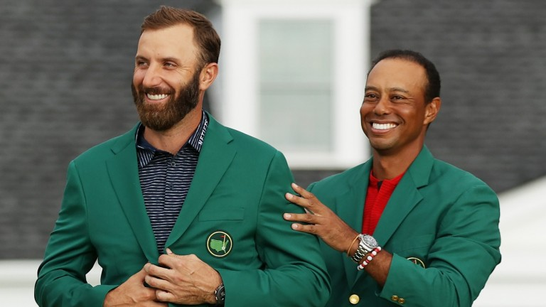 Dustin Johnson receives his Green Jacket from Tiger Woods