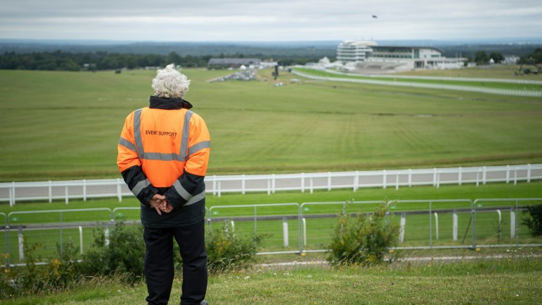 A security worker looks out over a locked-down Epsom racecourse on Derby day in 2020