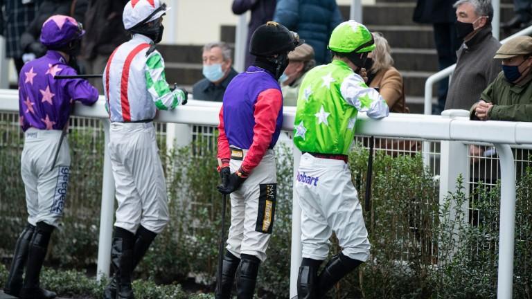 Jack Tudor (black cap) and Emir Sacree's jockey Joe Anderson (lime colours) talk pre-race tactics with Nicky Henderson