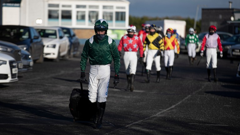 Bryan Cooper dragging his kit to the weighing room at Tramore, with many jockeys now having to disinfect equipment and store it at home