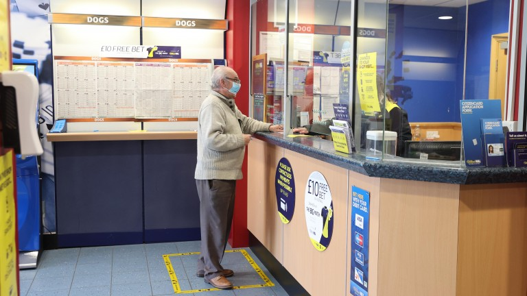 A customer places a bet socially distanced after betting shops opened on April 12