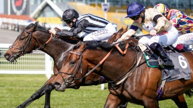 NEWBURY, ENGLAND - APRIL 18: Pat Dobbs riding Chindit (L, black cap) win The Watership Down Stud Too Darn Hot Greenham Stakes at Newbury Racecourse on April 18, 2021 in Newbury, England. Sporting venues around the UK remain under restrictions due to the C